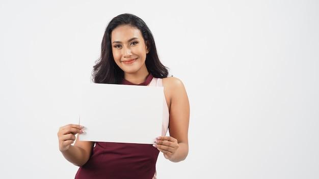 Aziatische mooie jonge vrouw met leeg blanco papier. een studioportret met witte achtergrond. lege ruimte voor tekst. ze heeft een bruine huid.