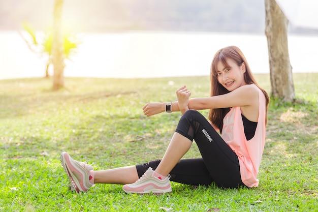 Aziatische mooie jonge vrouw ontspannende oefening in park