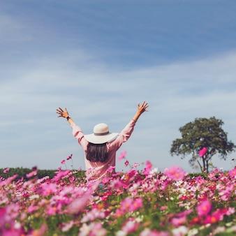 Aziatische mooie jonge vrouw wandelen en foto nemen in cosmos bloem veld landschap achtergrond. concept van reizen in het zomerseizoen in thailand.