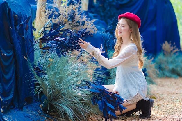 Aziatische mooie jonge vrouw zit en kijkt naar blauwe bloem in de natuurlijke tuin van café.