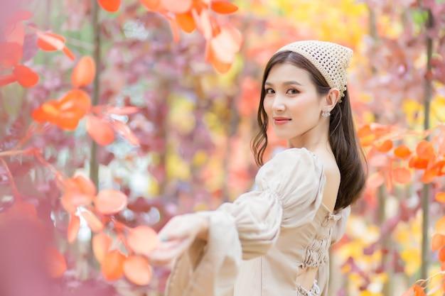 Aziatische mooie meid die lichtbruine jurk draagt, staat en lacht vrolijk met sinaasappelbos
