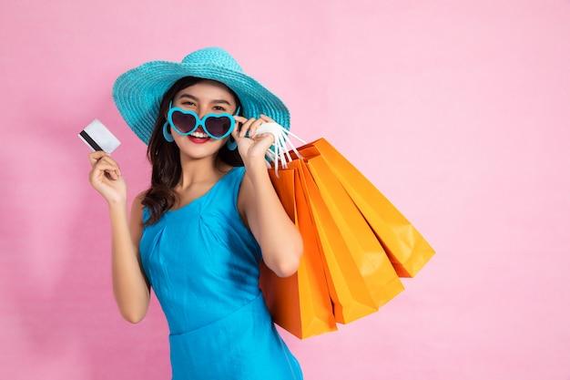 Aziatische mooie meisjesholding het winkelen zakken terwijl greepcreditcards en zonnebril het winkelen concept.