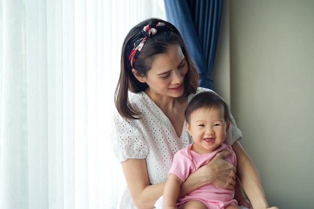 Aziatische mooie moeder die haar leuke baby in haar wapens houdt die dichtbij het venster zitten.