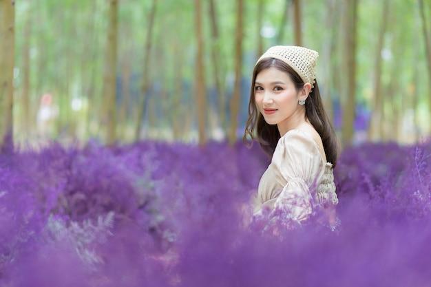 Aziatische mooie vrouw die een crèmekleurige jurk draagt, zit op de grond en kijkt naar de lavendelbloementuin