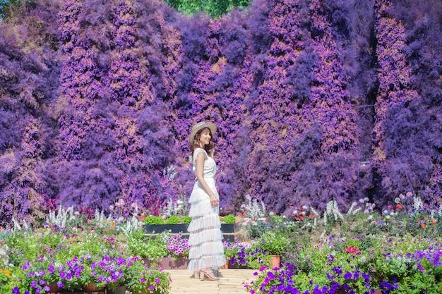 Aziatische mooie vrouw die een witte jurk en hoed draagt, staat tussen de paarse bloementuin