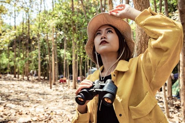 Aziatische mooie vrouw die er natuurlijk uitziet en een verrekijker gebruikt in het openbare park