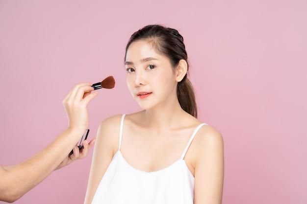 Aziatische mooie vrouw die hebbend een make-up door andere make-upkunstenaarmeisje van kant bevinden zich