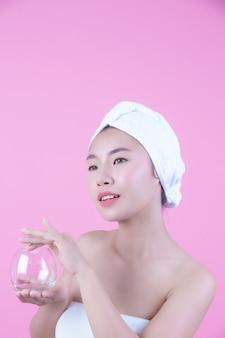 Aziatische mooie vrouw die het gezicht op een roze achtergrond, de kosmetiek en het kuuroord afvegen.
