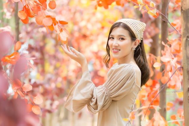 Aziatische mooie vrouw die lichtbruine jurk draagt, staat en lacht vrolijk met oranje bos (oranje verlof).