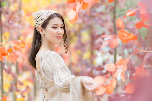 Aziatische mooie vrouw die lichtbruine jurk draagt, staat en lacht vrolijk met sinaasappelbos