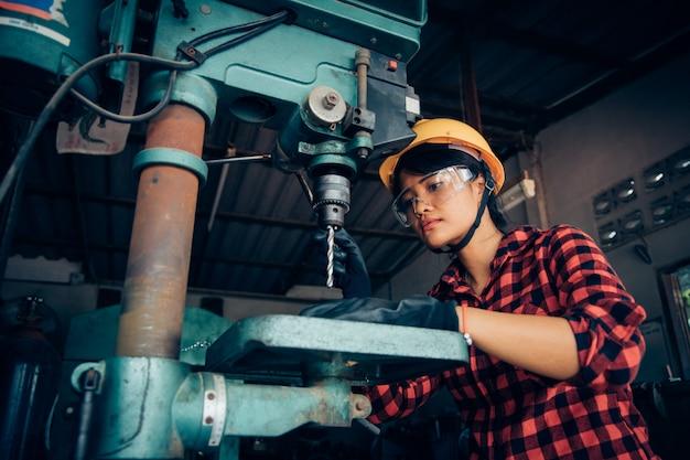 Aziatische mooie vrouw die met machine in de fabrieksingenieur en de werkende vrouwenconcept of vrouwendag werken