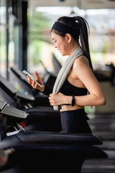 Aziatische mooie vrouw die sportkleding en smartwatch draagt, rust op de loopband, gebruikt smartphone en smartwatch workout-app en luistert naar muziek in moderne sportschool