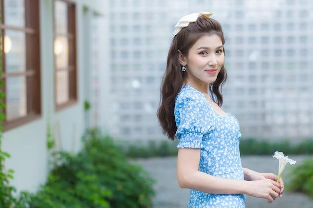 Aziatische mooie vrouw heeft donkerbruin haar in mooie blauwe jurk met margriet