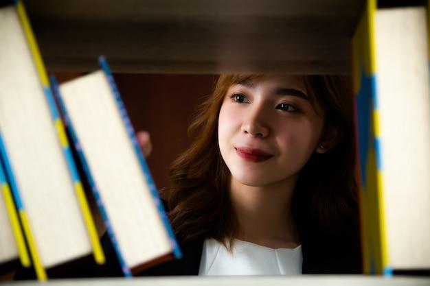 Aziatische mooie vrouw in bibliotheek