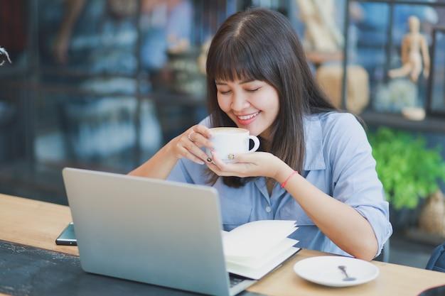 Aziatische mooie vrouw in blauw shirt met behulp van laptop en koffie drinken