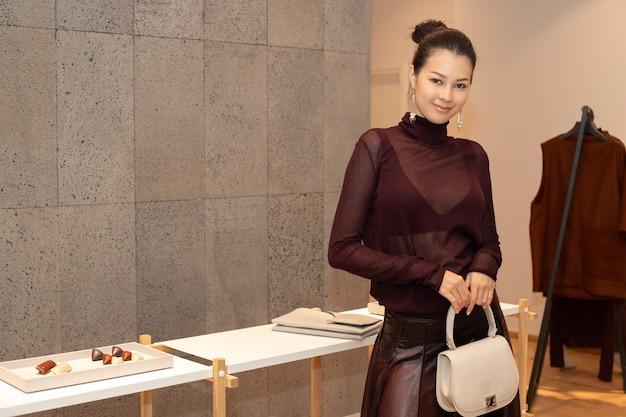 Aziatische mooie vrouw in donkerpaarse sexy jurk presenteert nieuwe collectie met handtasrugzak in modewinkel die net merknieuws opent voor de winterherfst als minimale stijl