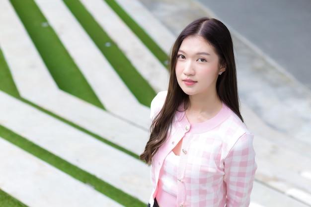 Aziatische mooie vrouw in een roze en wit gestreepte jas staat op het groene gras en de trap