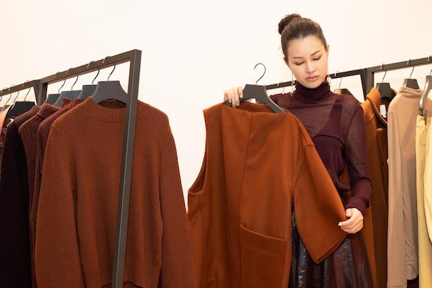Aziatische mooie vrouw in jurk selecteert nieuwe collectie op oranje groen aardetoon kledingrek in modewinkel die net merknieuws opent voor de winterherfst als minimale stijl