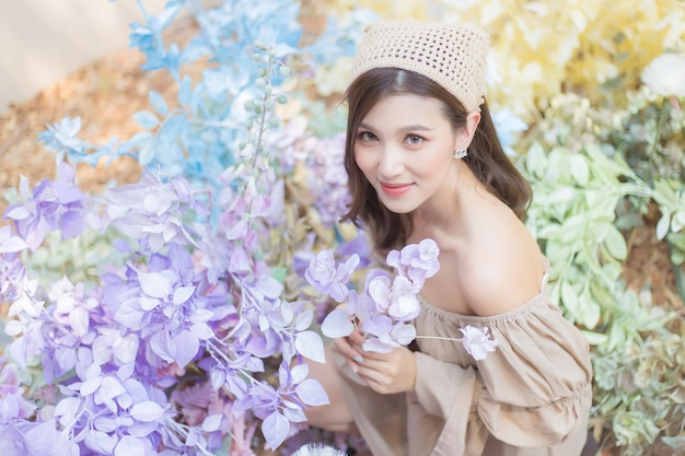 Aziatische mooie vrouw in mooie jurk lacht terwijl ze een bloemboeket in haar handen houdt