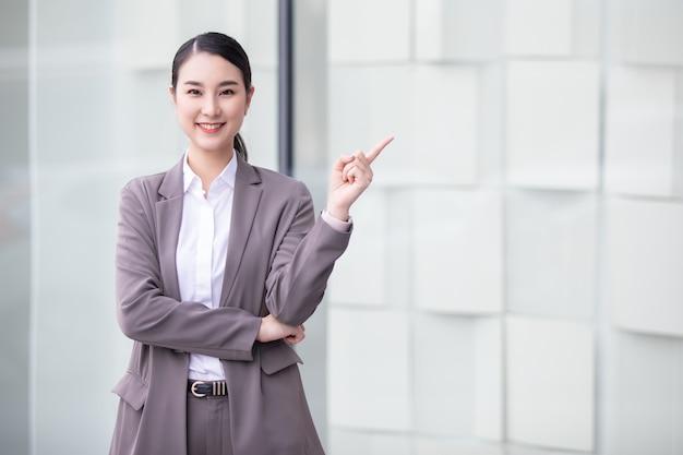 Aziatische mooie vrouw in pak wit t-shirt en witte broek die blij blij gezicht met exemplaarruimte beweren