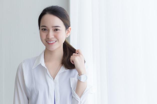 Aziatische mooie vrouw in wit overhemd lacht en staat in de buurt van raam met wit gordijn.