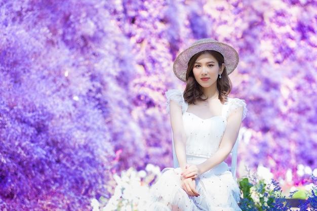 Aziatische mooie vrouw in witte jurk draagt een witte hoed en zit tussen de paarse bloementuin