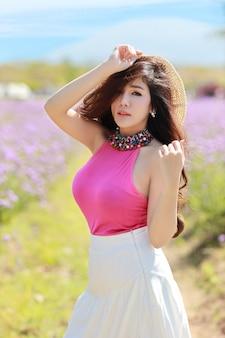 Aziatische mooie vrouw, lang haar in schattige jurk op verbena ingediend in de winter met blauwe lucht. reizen in de natuur buiten concept