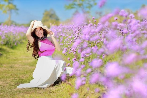 Aziatische mooie vrouw, lang haar in schattige jurk op verbena met blauwe hemel. mooi leuk meisjesportret dat van bloemen op de achtergrond van het bloemenlandbouwbedrijf geniet. reizen in de natuur buiten concept