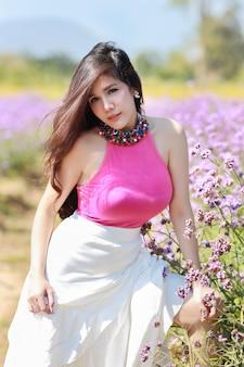 Aziatische mooie vrouw, lang haar in schattige jurk op verbena met blauwe hemel. mooi leuk meisjesportret dat van bloemen op de achtergrond van het bloemenlandbouwbedrijf geniet. reizen in de natuur concept