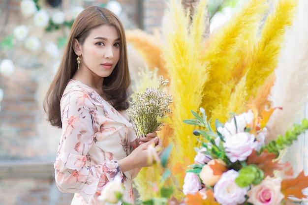 Aziatische mooie vrouw met bloemen met natuurlijke achtergrond.