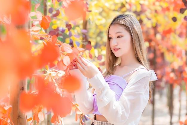 Aziatische mooie vrouw met bronzen haar staat tussen oranje bos in levendig en geluksthema.