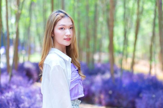 Aziatische mooie vrouw met een wit lang shirt lacht vrolijk en staat in de paarse bloementuin