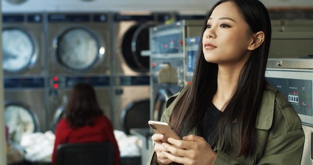 Aziatische mooie vrouw met lang donker haar die en bericht op smartphone tikken texting terwijl status in de ruimte van de wasserijdienst. mooie vrouw die op telefoon typen en op te wassen kleren wachten.