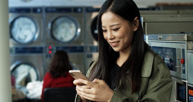 Aziatische mooie vrouw met lang donker haar sms-bericht op smartphone terwijl je in de wasruimte. mooie vrouw die op telefoon typen en op kleren wachten om in openbare wasserette te wassen.