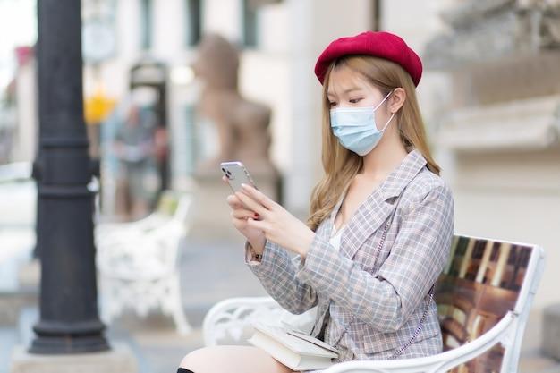 Aziatische mooie vrouw met pak en rode dop houdt smartphone in haar handen terwijl ze op een bankje in het park zit terwijl ze een medisch gezichtsmasker draagt in een nieuw normaal levensstijlconcept.
