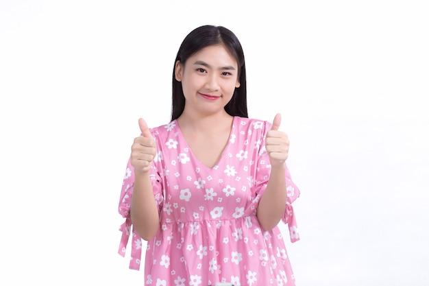 Aziatische mooie vrouw met zwart lang haar in een roze jurk glimlachend met een goed humeur duimen omhoog