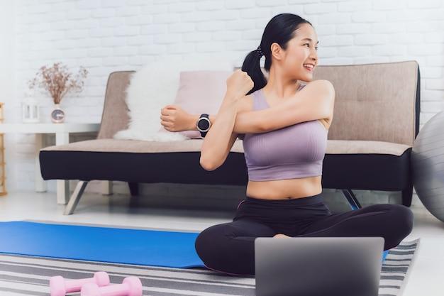 Aziatische mooie vrouw oefenen thuis en kijken naar trainingsvideo op laptop.