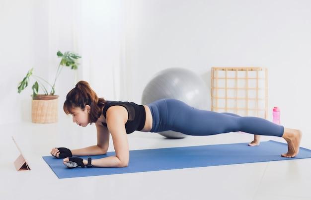 Aziatische mooie vrouw oefenen thuis en kijken naar trainingsvideo op tablet