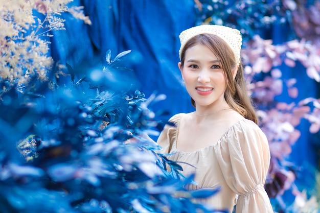 Aziatische mooie vrouw staat bewondert met bloem in blauwe tuin en bos als achtergrond.