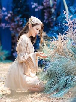 Aziatische mooie vrouw zit op de grond en bewondert met bloem in blauwe tuin en bos als achtergrond