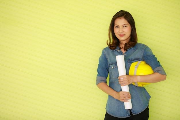 Aziatische mooie vrouwelijke ingenieur die een witte papierrol draagt en een gele veiligheidshelm vasthoudt, staande voor kleurrijke groene achtergrondgeluiden