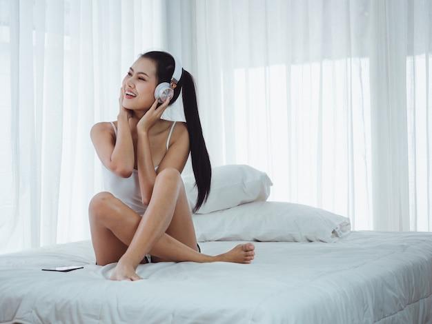 Aziatische mooie vrouwen die aan muziek in bed luisteren