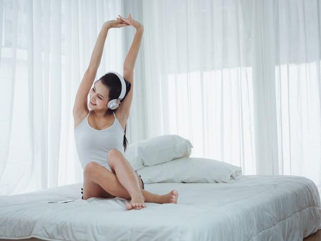 Aziatische mooie vrouwen die aan muziek luisteren en zich in bed uitrekken