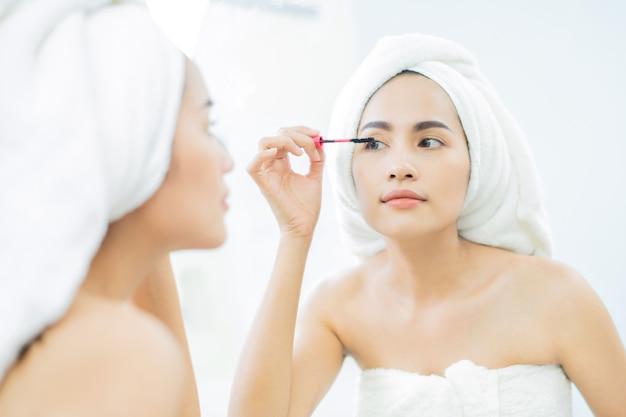 Aziatische mooie vrouwen die zwarte mascarawimpers na het baden toepassen