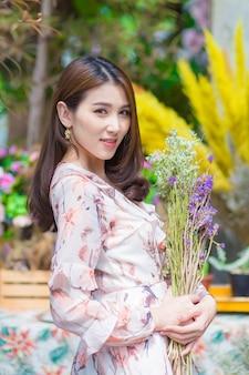Aziatische mooie vrouwenglimlach die bloemen met natuurlijke achtergrond houdt.