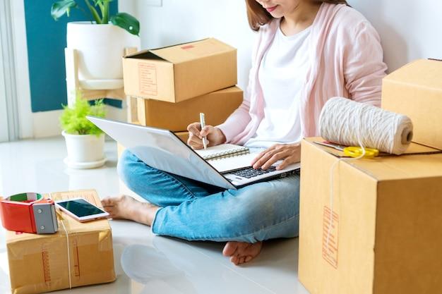 Aziatische mooie vrouwenondernemer die orde op haar laptop controleert en aan memorandumboek schrijft. online verkopen, zaken en technologie, nieuw normaal concept.