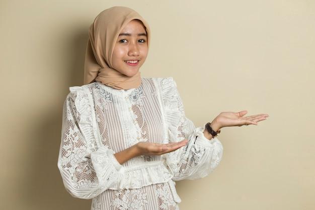 Aziatische moslim hijab vrouw met hand punt op lege ruimte