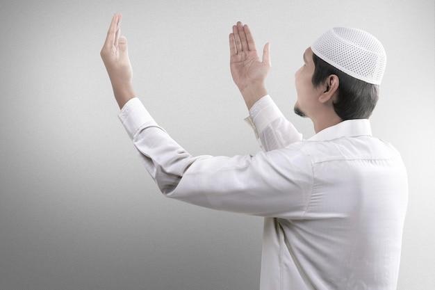 Aziatische moslim man bidden met bidparels op zijn handen met mist achtergrond