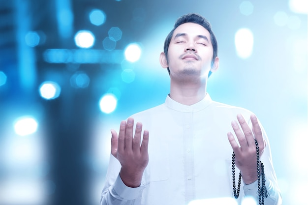Aziatische moslim man bidden met bidparels op zijn handen met wazig licht