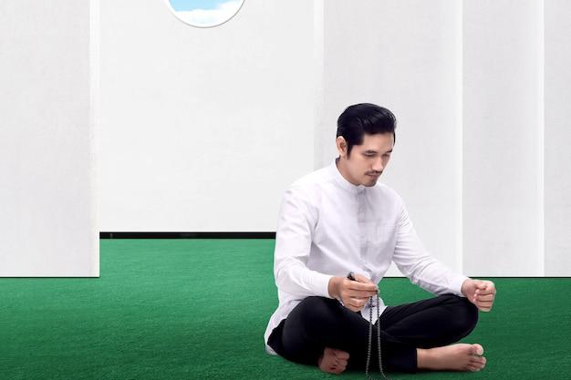 Aziatische moslim man bidden met bidparels op zijn handen op de moskee